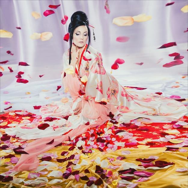 Arbeiten sie porträt eines jungen schönen brunette in der japanischen art wie eine geisha um Premium Fotos