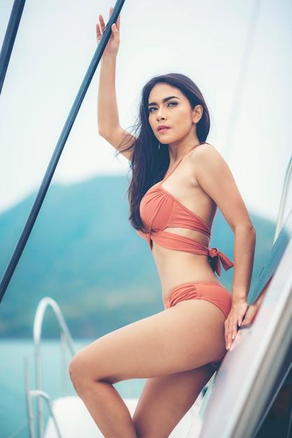 Arbeiten sie sommerfoto im freien des sexy mädchens mit dem dunklen haar im luxuriösen bikini um, der auf yacht im meer sich entspannt Premium Fotos