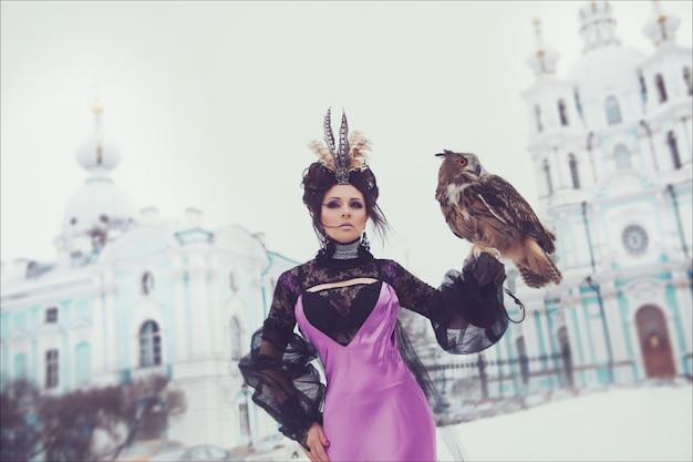 Arbeiten sie winterporträt eines schönen brunette in einem langen lila kleid mit einer uhu um. kreative frisur und make-up Premium Fotos