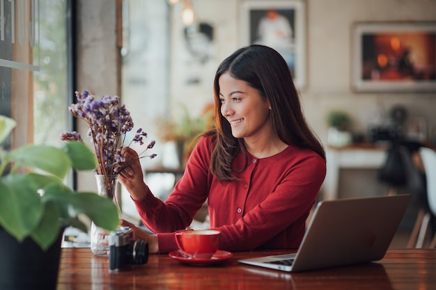 Arbeitender und trinkender kaffee des asiatischen geschäftsmädchens im café mit laptop Premium Fotos