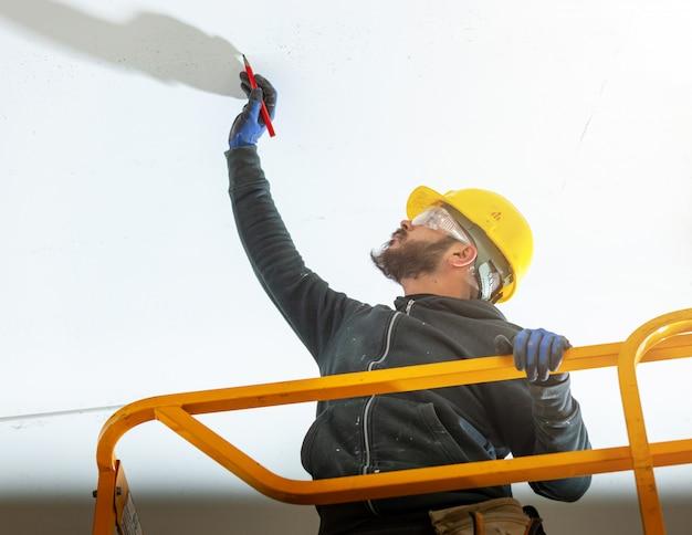 Arbeiter baut eine gipskartonwand. Premium Fotos