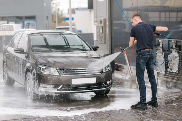Arbeiter, der auto mit hochdruckwasser reinigt. Premium Fotos