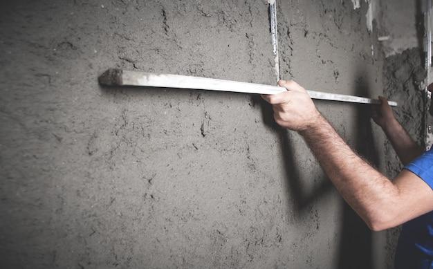 Arbeiter, der ebenes werkzeug hält verputzwand bauarbeiten arbeit heimindustrie Premium Fotos
