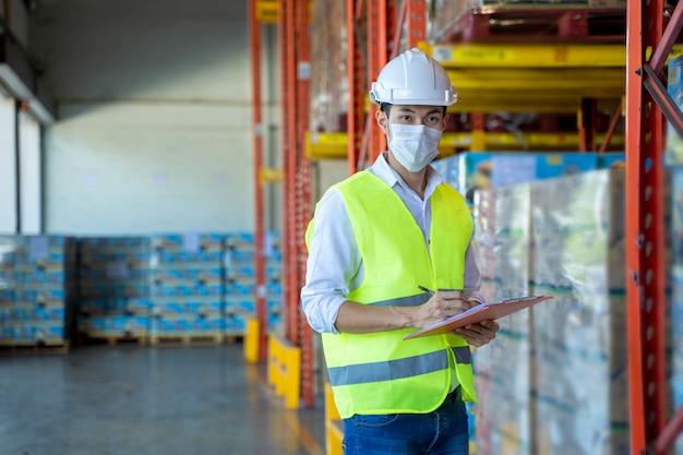 Arbeiter, der eine schutzmaske trägt, um sich vor covid-19 zu schützen und das produkt in einem großen lager zu überprüfen. Premium Fotos