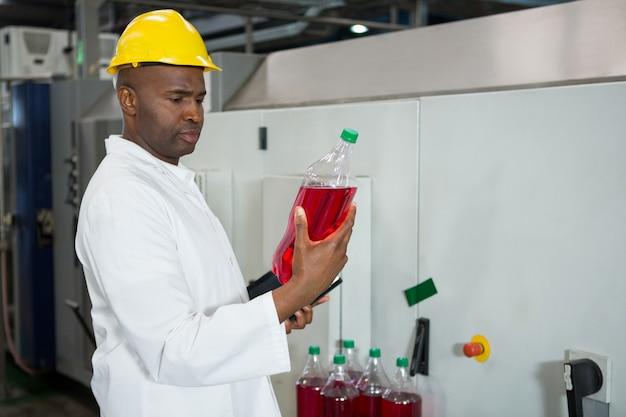 Arbeiter, der flaschen in der saftfabrik untersucht Kostenlose Fotos