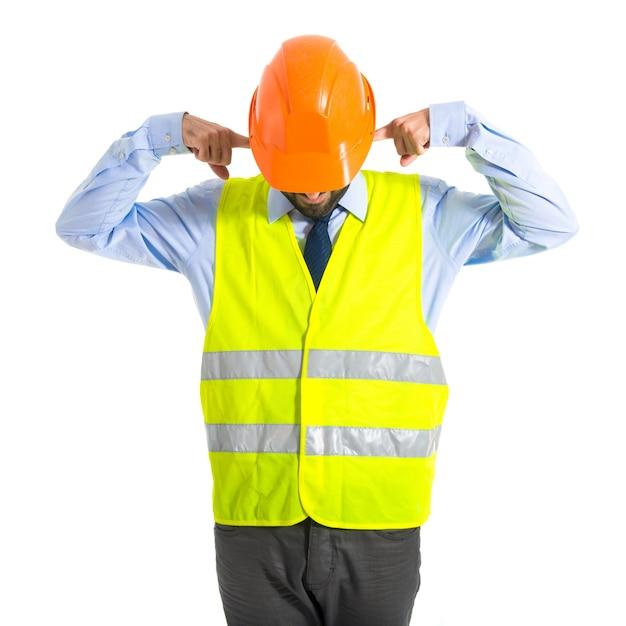Arbeiter, der seine ohren bedeckt Kostenlose Fotos