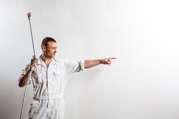 Arbeiter, der spritzpistole auf weißer wand hält. Kostenlose Fotos