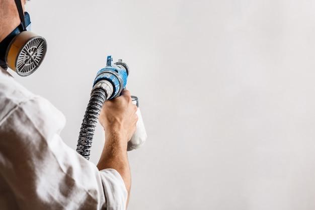 Arbeiter, der wand mit spritzpistole in der weißen farbe malt. Kostenlose Fotos
