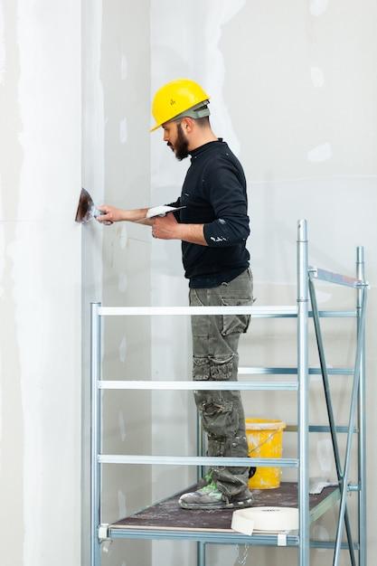 Arbeiter gipskartonwand verputzen. Premium Fotos