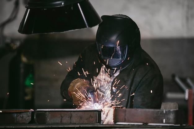 Arbeiter in der fabrik im helm ist aus eisen im schweißprozess helle funken Premium Fotos