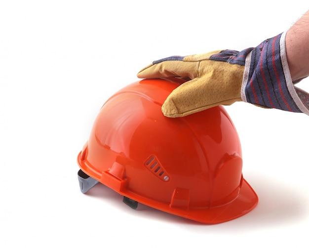 Arbeiter in schutzhandschuhen hält einen orangefarbenen schutzhelm in der hand. Premium Fotos