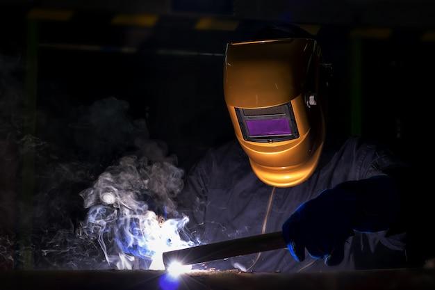 Arbeiter über schweißer stahl elektrisches schweißgerät verwenden. Premium Fotos