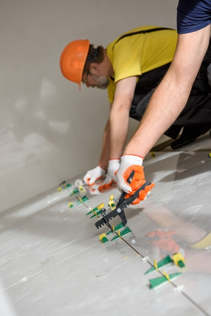 Arbeiter verwenden plastikklammern und keile, um die großen keramikfliesen auf dem boden auszurichten Premium Fotos