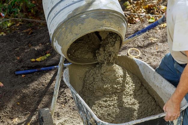 Arbeiter verwendet einen beton, der im betonmischer bei hochbauarbeiten hergestellt wird Premium Fotos