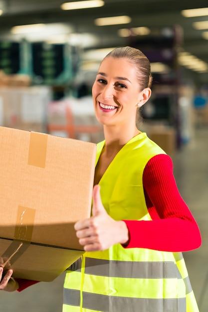 Arbeitnehmerin mit schutzweste hält das paket und steht am lager der speditionsfirma Premium Fotos