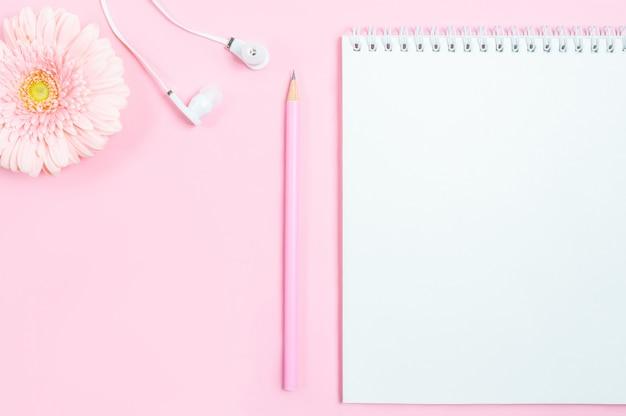 Arbeitsbereich: notizblock, bleistift, kopfhörer und gerberablume auf rosa hintergrund. Premium Fotos