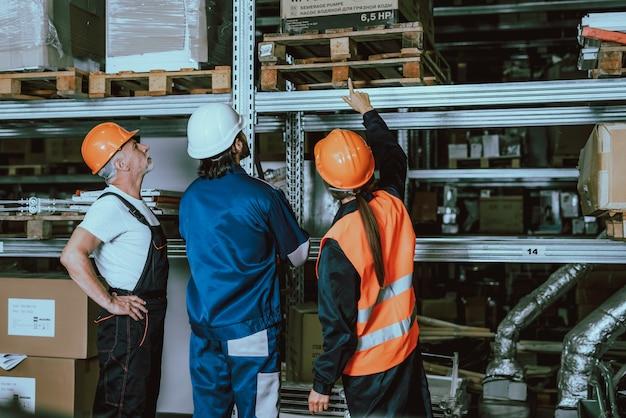 Arbeitskräfte, die uniform und schutzhelme im lager tragen Premium Fotos