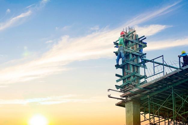Arbeitskraft, die an gebäude vom hochland und von der stahlstange an der baustelle steht und arbeitet. Premium Fotos