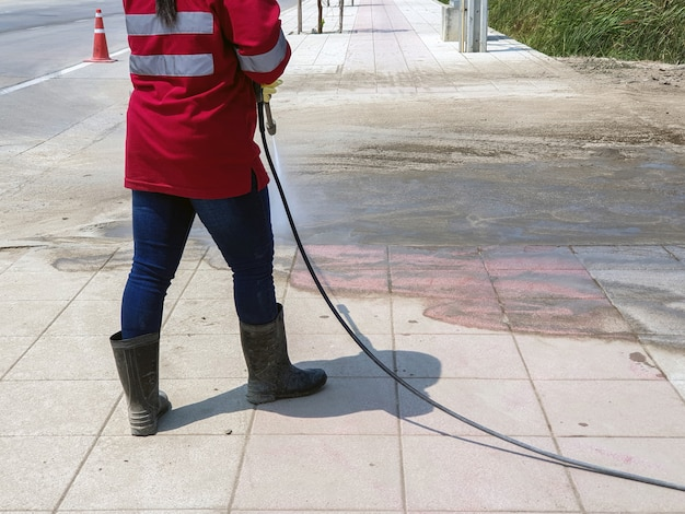 Arbeitskraft, die betonblockboden durch hochdruckwasserstrahl säubert Premium Fotos