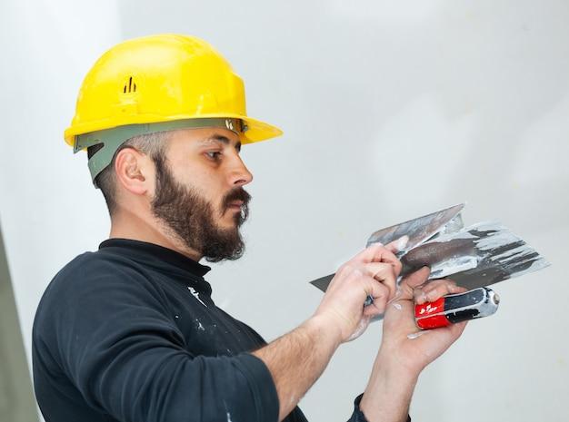 Arbeitskraft, die gipskartonwand vergipst. Premium Fotos