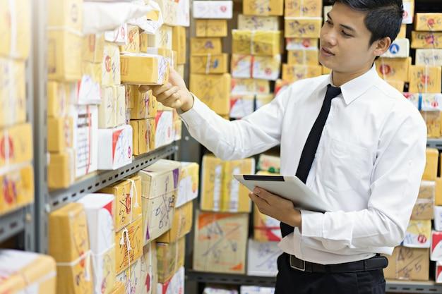 Arbeitskraft, die paket unter verwendung der tablette im lager überprüft. Premium Fotos