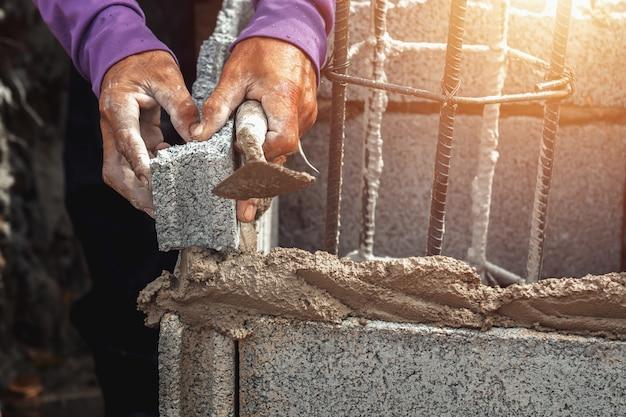 Arbeitskraft, die ziegelsteine in baustelle installiert Premium Fotos