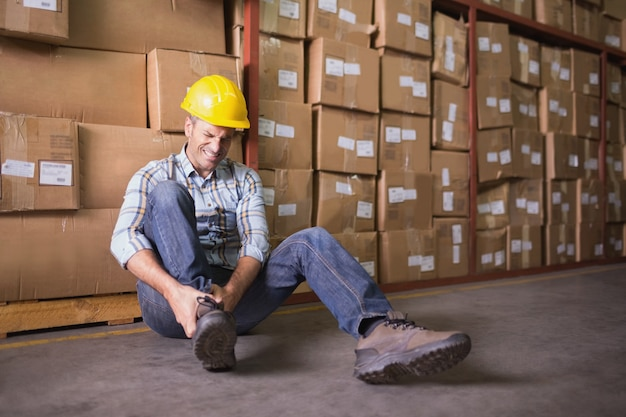 Arbeitskraft mit verstauchtem knöchel auf boden im lager Premium Fotos