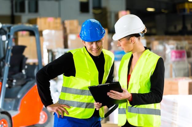 Arbeitskraft oder lagerverwalter und sein mitarbeiter mit klemmbrett am lager der spedition, zeigend Premium Fotos