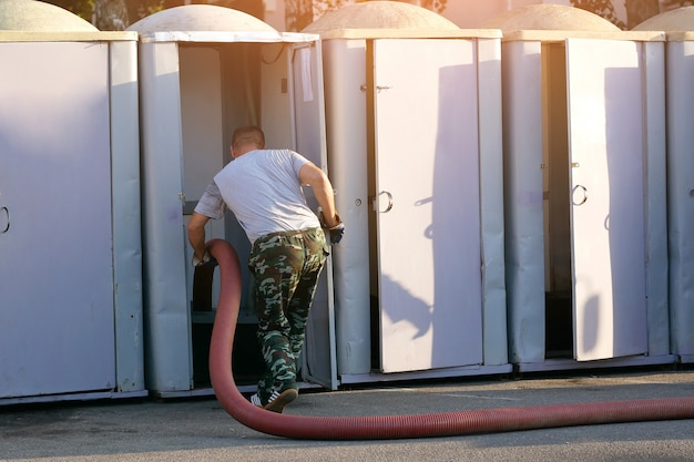 Arbeitskraft säubert die straßentoiletten und pumpt abwasser heraus Premium Fotos
