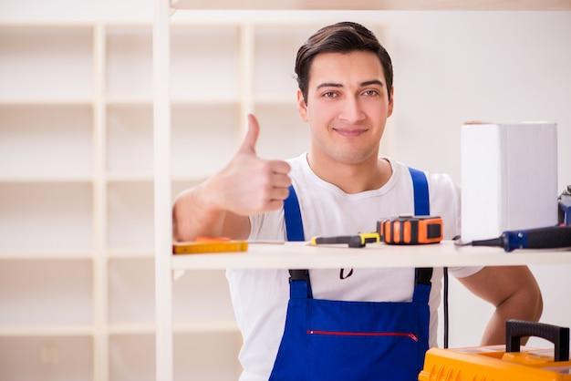 Arbeitskraftmann, der zusammenbauendes bücherregal repariert Premium Fotos