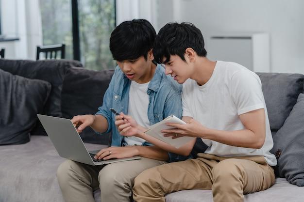 Arbeitslaptop der jungen asiatischen homosexuellen paare am modernen haus. die glücklichen männer asiens lgbtq + entspannen sich den spaß, der computer verwendet und zusammen ihre finanzen im internet analysiert, während lügensofa im wohnzimmer am haus. Kostenlose Fotos