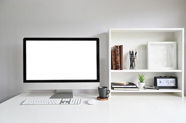 Arbeitsplatz-computer auf schreibtisch und büchern, fotorahmen und büchern auf regalen. Premium Fotos