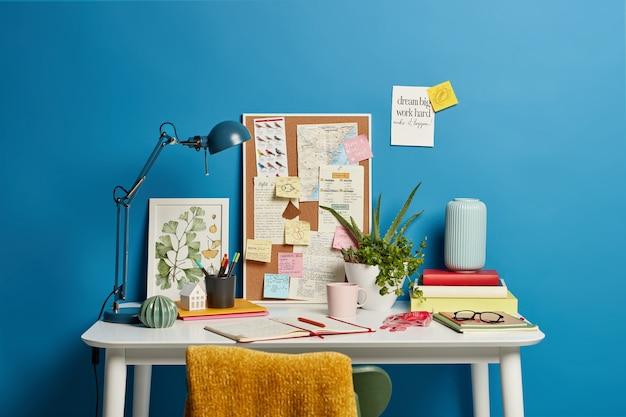 Arbeitsplatz des studenten. desktop mit lampe, geöffnetem notizbuch, briefpapier und grüner zimmerpflanze, tasse kaffee haftnotizen auf blau. heimbüro Kostenlose Fotos