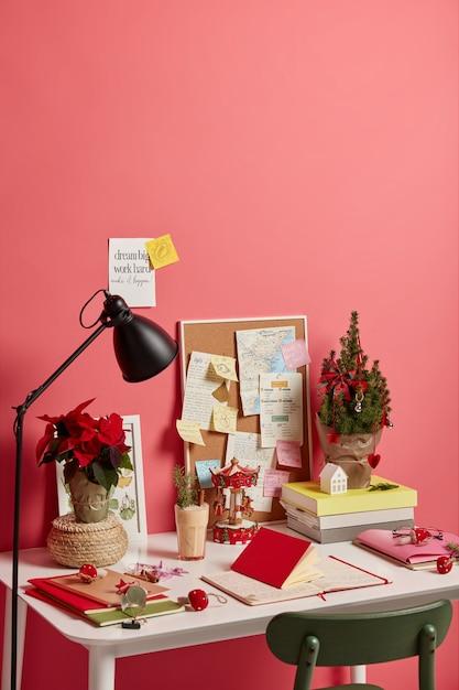 Arbeitsplatz mit geschmücktem weihnachtsbaum, eierlikörgetränk im glas, verschiedene notizen mit zukunftsplänen und motivationsphrasen, lokalisiert auf rosa hintergrund Kostenlose Fotos
