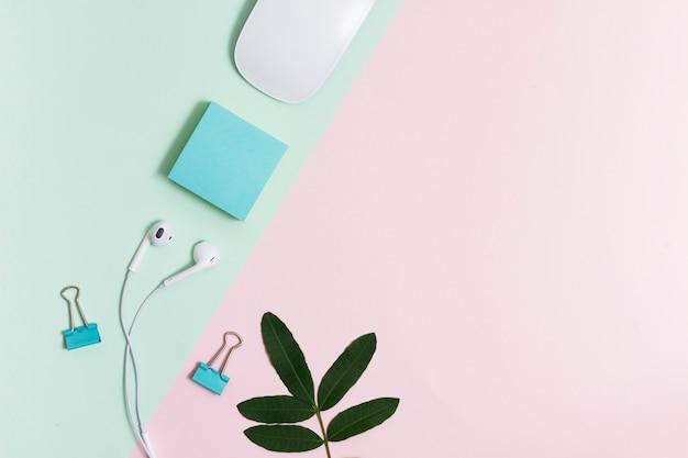 Arbeitsplatz mit kopfhörern und maus auf rosa und grünem hintergrund Kostenlose Fotos