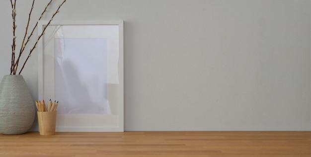 Arbeitsplatz mit mock-up-frame und büromaterial auf holztisch und weiße wand Premium Fotos