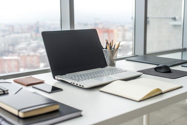 Arbeitsplatz mit notebook-laptop bequemer arbeitstisch in bürofenstern und blick auf die stadt. Premium Fotos