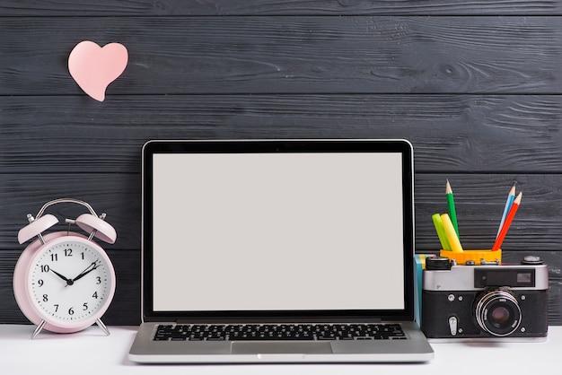 Arbeitsplatz mit offenem laptop auf modernem hölzernem schreibtisch mit kamera und wecker Kostenlose Fotos
