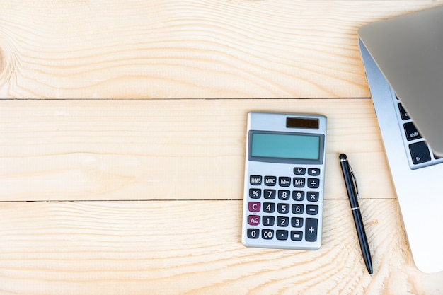 Arbeitsplatz mit taschenrechner, schwarzer stift, laptop auf dem kiefernholzhintergrund. Premium Fotos