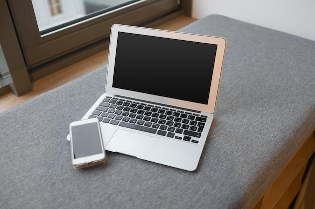Arbeitsplatz nahe dem fenster mit laptop und computer, kopienraum Premium Fotos