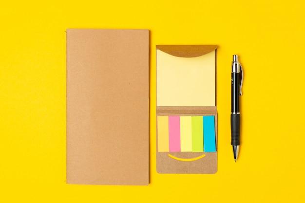 Arbeitsplatz, notizblock, haftnotizen und stift auf hellem gelb Premium Fotos