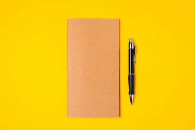 Arbeitsplatz, notizblock und stift auf hellem gelb Premium Fotos