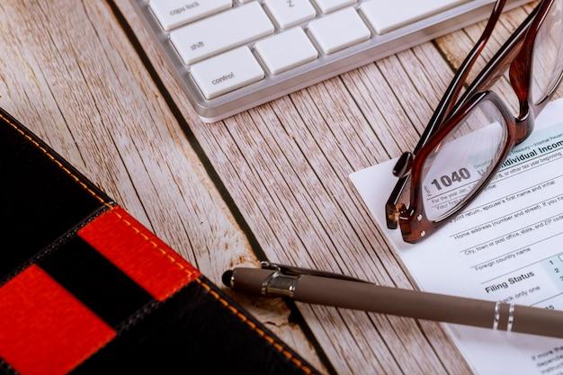 Arbeitsplatz schreibtisch tisch im büro des buchhalters us einkommenssteuer 1040 formular mit brille und stift auf der computertastatur Premium Fotos