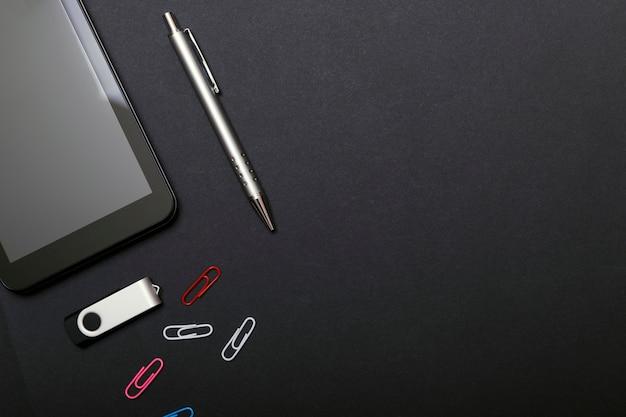 Arbeitsplatz, tabletpc und smartphone auf schwarzer tabelle. Premium Fotos