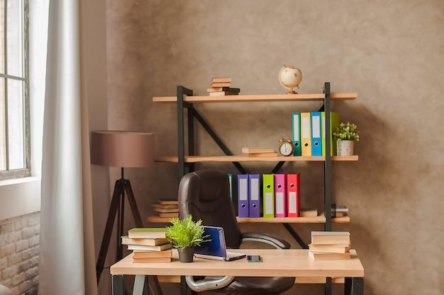 Arbeitsplatz zu hause. rack mit ordnern und tisch mit laptop-nahaufnahme und kopierraum. Premium Fotos