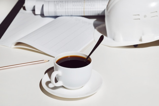 Arbeitsplatzarchitekt. ein tasse kaffee, ein sturzhelm und lichtpausen auf weißer tabelle. Premium Fotos