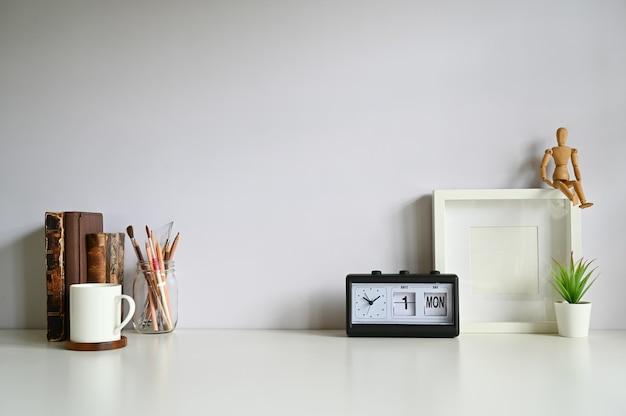 Arbeitsplatzfotorahmen, kaffee, warnung, bücher mit anlage verzieren auf weißer tabelle. Premium Fotos