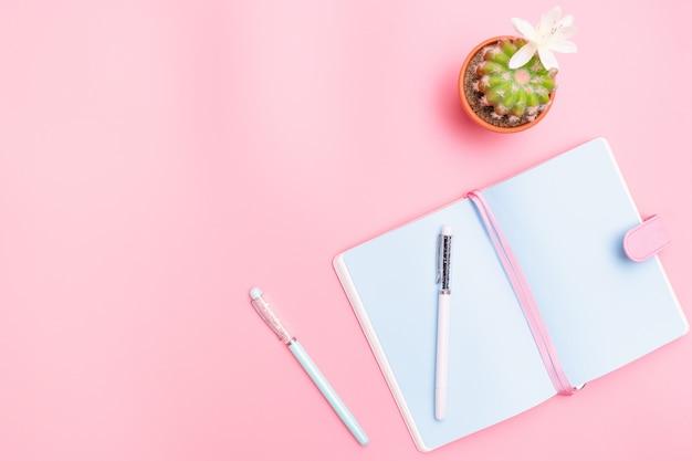 Arbeitsplatzschreibtisch-büroartikel mit kaktus auf rosa pastellhintergrund Premium Fotos