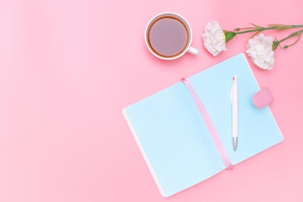 Arbeitsplatzschreibtisch-bürozubehör, heißer tee und weiße blume auf rosa pastellhintergrund Premium Fotos