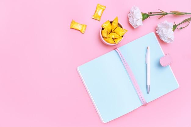 Arbeitsplatzschreibtischbüroartikel, -süßigkeit und -blume auf rosa pastellhintergrund Premium Fotos